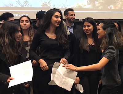 Students, holding sheets of paper, getting ready to perform at End of Quarter Event